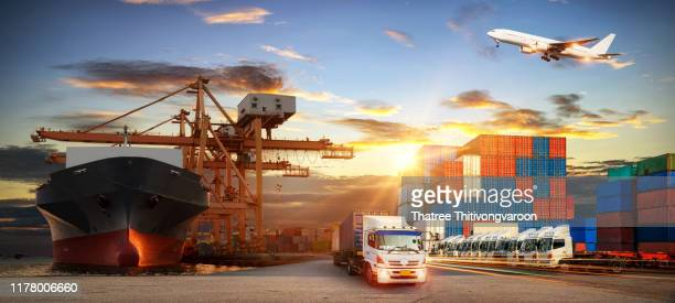 container truck in ship port for business logistics and transportation of container cargo ship and cargo plane with working crane bridge in shipyard at sunrise, logistic import export and transport industry background - 貨物運送 ストックフォトと画像