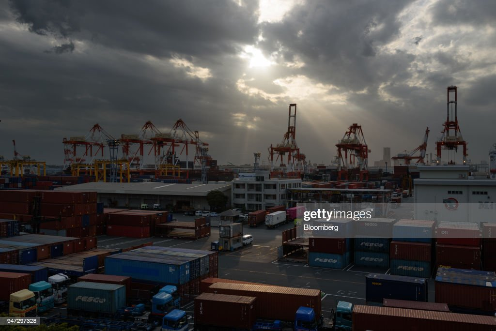 Containers and gantry cranes stand at a shipping terminal at dusk in Yokohama, Japan, on Monday, April 16, 2018. Japan and China held their first high-level economic dialogue in almost eight years on April 16 against a backdrop of trade threats from the U.S. Photographer: Akio Kon/Bloomberg via Getty Images