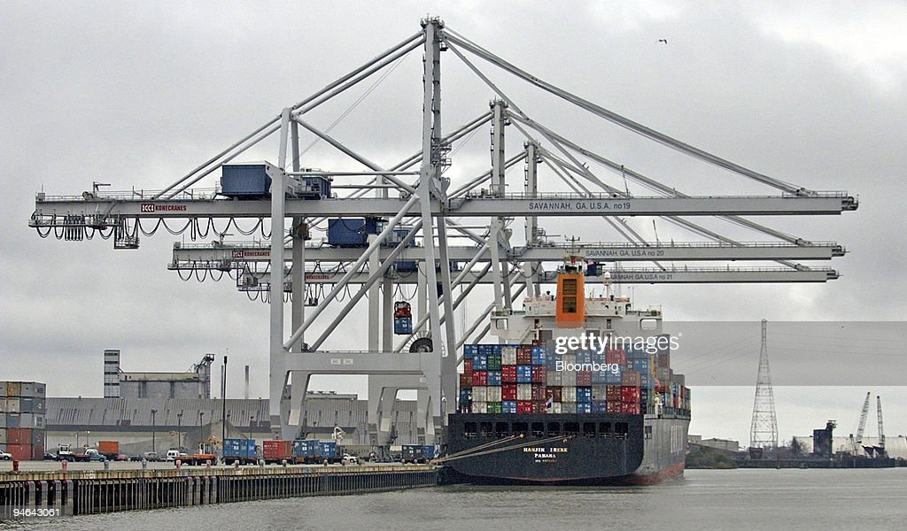 Containers are lifted off trucks onto a container ship at