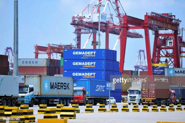 Containers are transferred at a port in Qingdao in China's eastern Shandong province on July 6 2018 Punishing US tariffs on Chinese imports took...