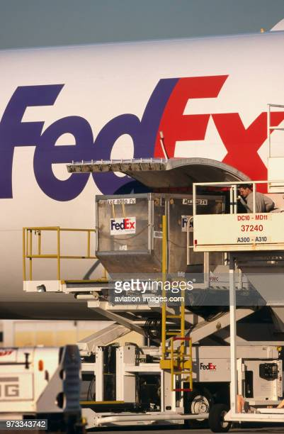 LD3 containers being loaded into lower side cargo door of a FedEx Airbus A300600 freighter