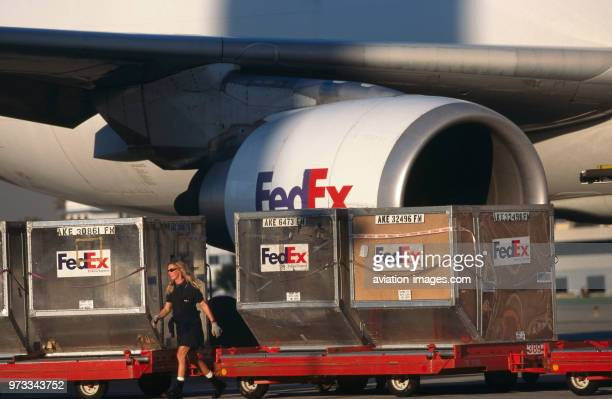 LD3 containers being loaded onto trolleys with a GE CF680 engineintake of a FedEx Airbus A300600 freighter behind