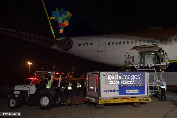Containers carrying doses of the Oxford/AstraZeneca vaccine with a banner reading Brazil immunized. We are an only nation are unloaded from a cargo...