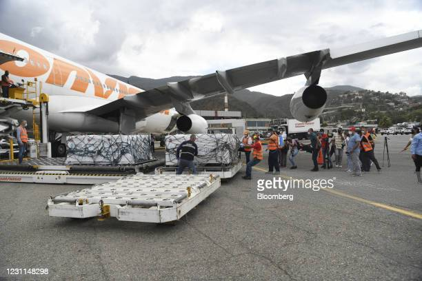 Containers carrying Russian Sputnik V Covid-19 vaccines are moved from a Conviasa Airlines aircraft at Simon Bolivar International Airport in...