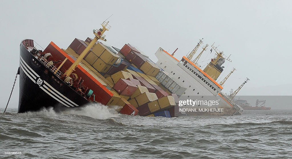 Containers fall from the deck of the damaged cargo ship MSC Chitrain in the Arabian Sea off the Mumbai coast on August 9, 2010. The Indian coastguard was trying on Monday to contain oil from a badly-listing container ship that collided with another vessel off the Indian coast near the city of Mumbai, a defence ministry spokesman said. Some 200 containers have fallen from the ship and are being collected. Environmental emergency teams have been put on alert to mobilise for a clean-up operation, while fishermen have been told not to put to sea until the all-clear has been given. AFP PHOTO/ Indranil MUKHERJEE