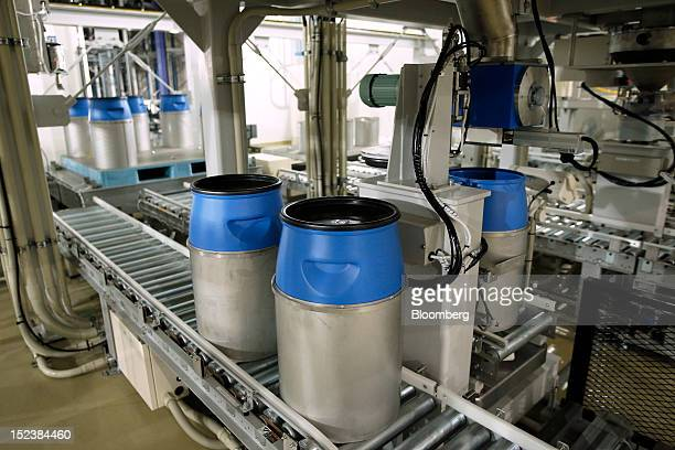 Containers move along the production line as they are filled with raw material at the JX Nippon Mining Metals Corp plant for making cathode materials...