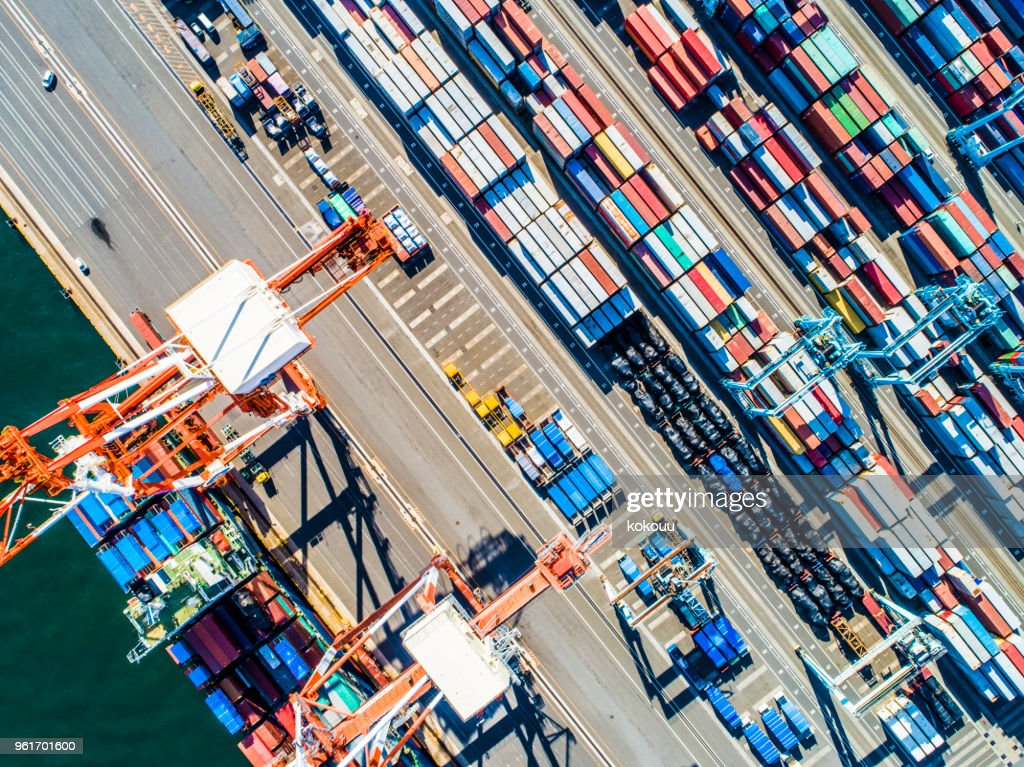Containers of various colors are lined next to the sea. : Stock Photo