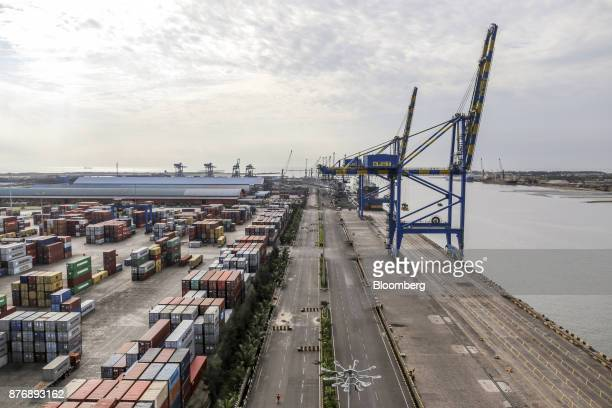 Containers sit stacked in a yard near gantry cranes at Krishnapatnam Port in Krishnapatnam Andhra Pradesh India on Saturday Aug 12 2017 Growth in...