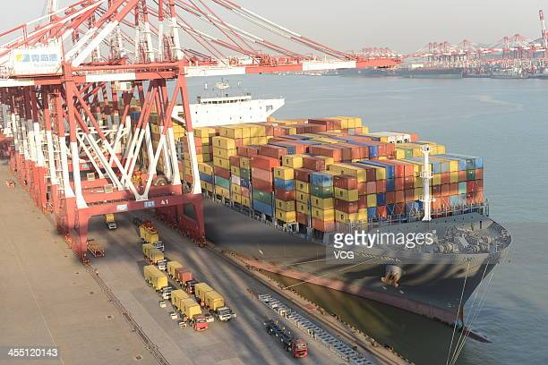 Containers sit stacked on a cargo ship berthed at Qingdao Port on December 10 2013 in Lianyungang China China's gross domestic product is likely to...