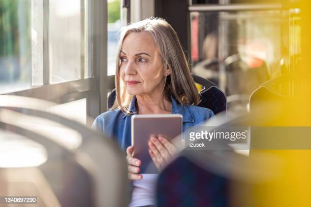 contemplated elderly woman traveling in bus - izusek stock pictures, royalty-free photos & images