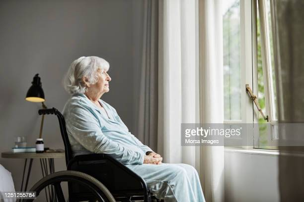 contemplated senior female sitting on wheelchair - one senior woman only stock pictures, royalty-free photos & images