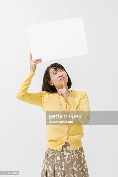 contemplated woman holding placard - alleen één mid volwassen vrouw stockfoto's en -beelden