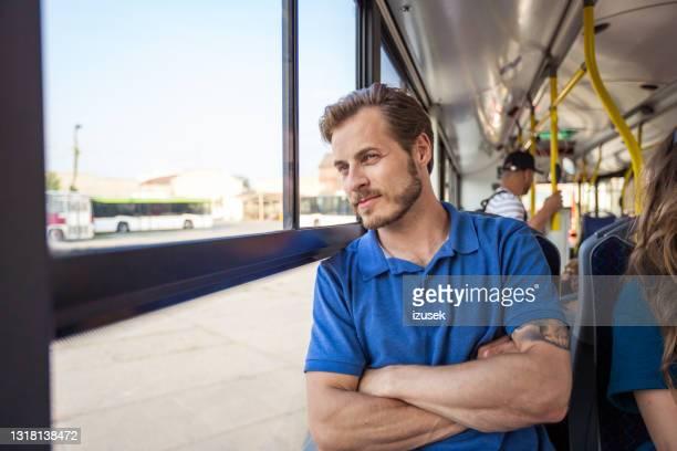 überlegter junger mann, der im bus unterwegs ist - izusek stock-fotos und bilder