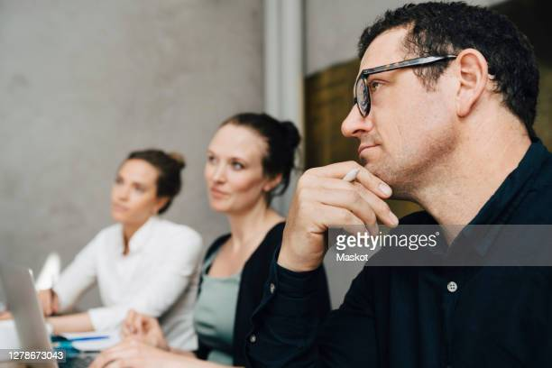 contemplating businessman with colleagues sitting at workplace - hand on chin stock pictures, royalty-free photos & images