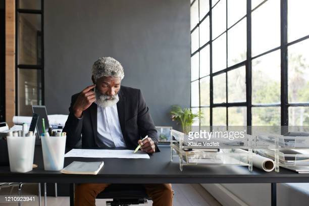 contemplating businessman working at office desk - business stock pictures, royalty-free photos & images
