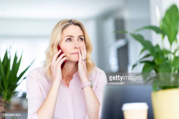 contemplating businesswoman talking on smart phone at home office - worried stock pictures, royalty-free photos & images
