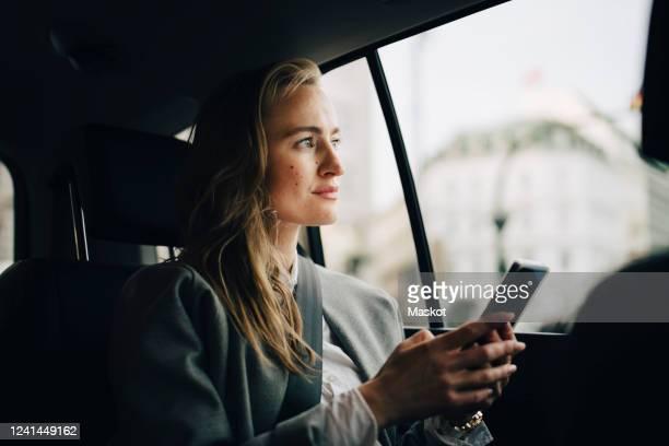 contemplating female entrepreneur with smart phone looking through window while sitting in taxi - finanzen stock-fotos und bilder