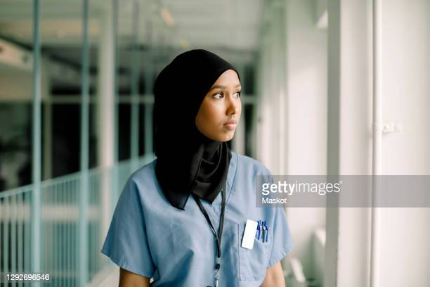 contemplating female nurse looking through window while standing in hospital corridor - islam stock pictures, royalty-free photos & images