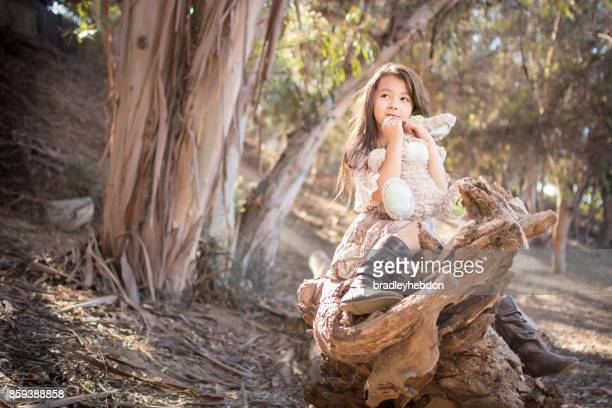 Contemplating girl sitting on log in forest with toy bunny
