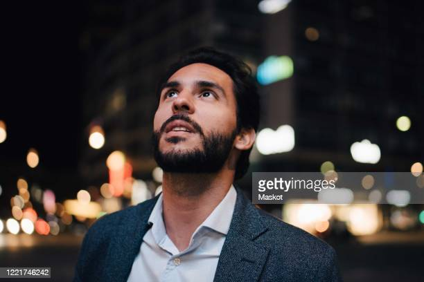 contemplating man looking up while standing in city at night - one man only stock pictures, royalty-free photos & images