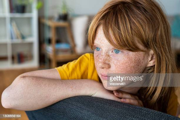 contemplating redhead girl sitting on chair at home - bangs hair stock pictures, royalty-free photos & images