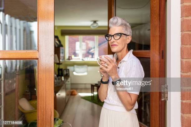 contemplating senior woman standing on doorway while drinking coffee at home - one senior woman only stock pictures, royalty-free photos & images