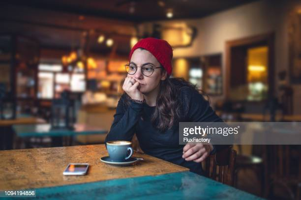 contemplating student sitting at a coffee shop - holiday stress stock pictures, royalty-free photos & images