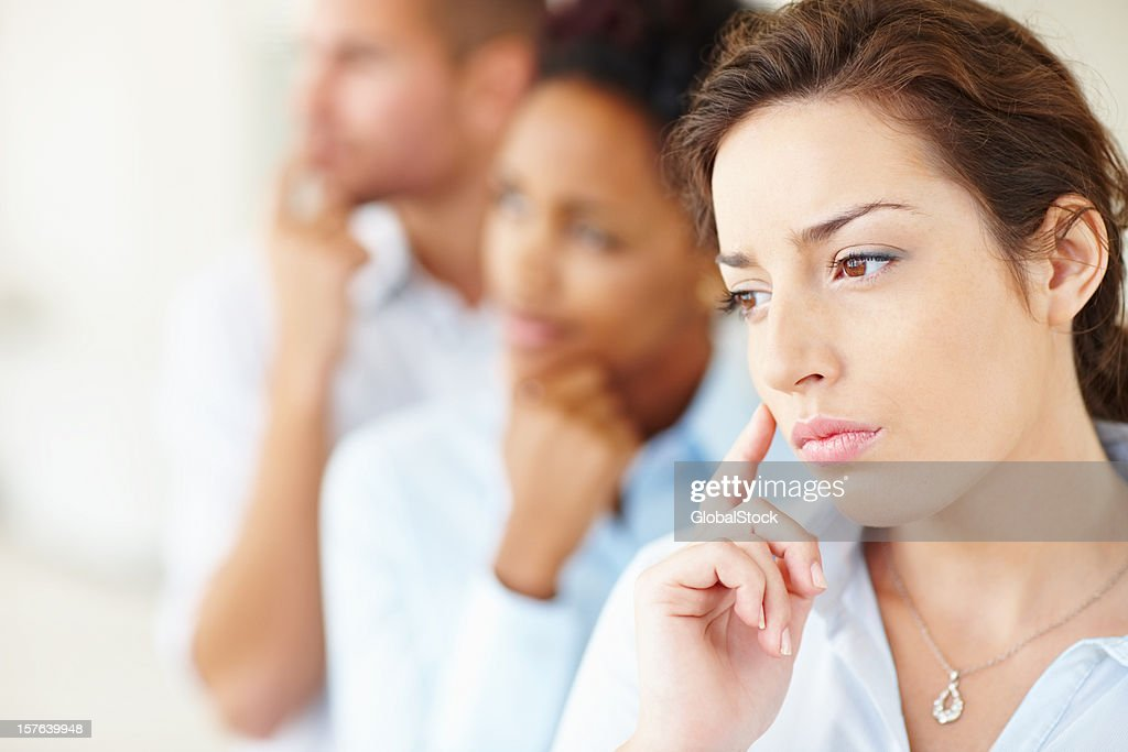 Contemplative business colleagues standing in a row : Stock Photo