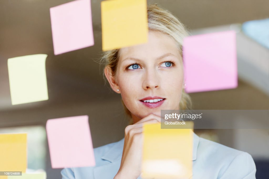 Contemplative business woman with sticky notes on glass window : Bildbanksbilder