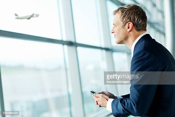 Contemplative Businessman Looking At An Airplane Taking Off.