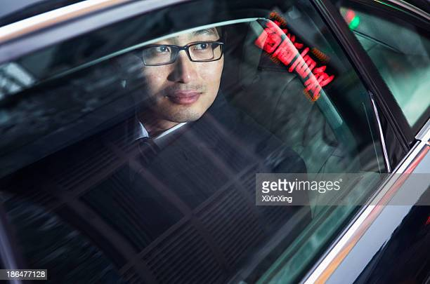 Contemplative businessman looking through car window at the night