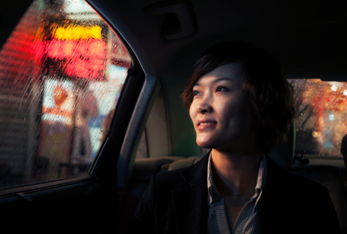 Contemplative Businesswoman looking out of car window through the rain at night in Beijing - gettyimageskorea