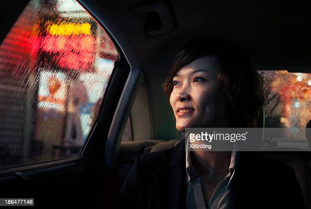 Contemplative Businesswoman looking out of car window through the rain at night in Beijing