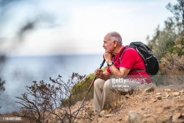 contemplative senior spanish male backpacker looking at view - mediterranean sea stock pictures, royalty-free photos & images