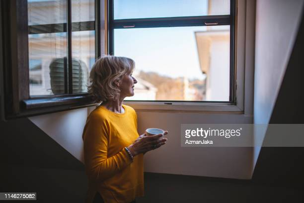 contemplative senior woman enjoying coffee and a quiet moment at a window - nook architecture stock pictures, royalty-free photos & images