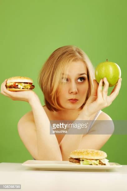 Entspannte Frau Holding Apple und Hamburger zu entscheiden