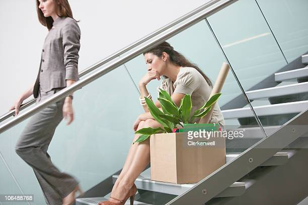 Contemplative woman with her colleague on staircase with cardboard box aside