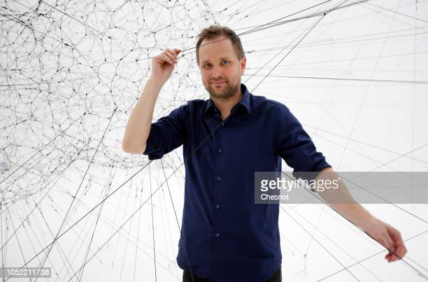Contemporary Argentinian artist Tomas Saraceno poses inside his artwork Algo Rithms prior to the opening of his exhibition ''On Air'' at the Palais...