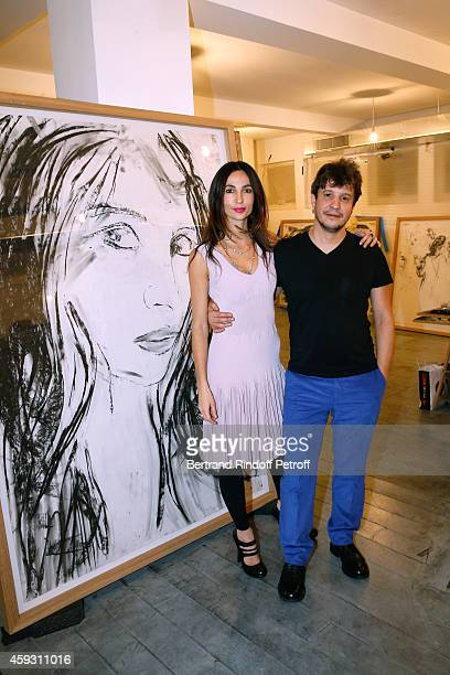 Contemporary artist Adel Abdessemed with his wife Julie posing in front of an Adel's work a portrait of his wife Julie attend Helene Cixous receives...