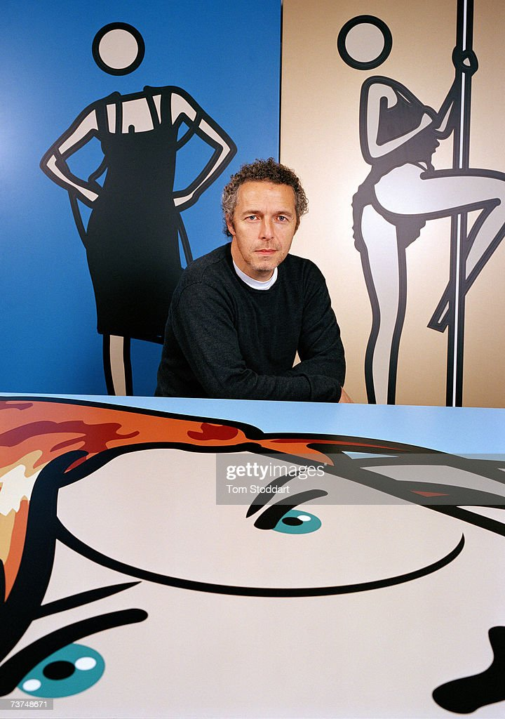 Contemporary artist Julian Opie photographed at his Shoreditch studio in London, and surrounded by his distinctive computerized art work. His highly stylised work, created using computer software involves the reduction of photographs or short films into figurative reproductions. In his portraiture, the human face is characterised by black outlines with flat areas of colour, and minimalised detail, where an eye become just the black circle of the pupil, and sometimes a head is represented by a circle with a space where the neck would be. Opie?s most famous design was for, Blur: The Best Of, album cover where the band members appear transformed into Opie's style.