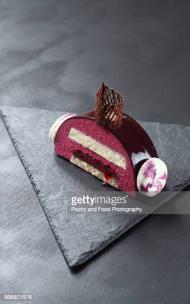 contemporary black currant chocolate yule log - yule log stock photos and pictures