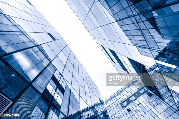 Contemporary glass skyscraper reflecting the blue sky