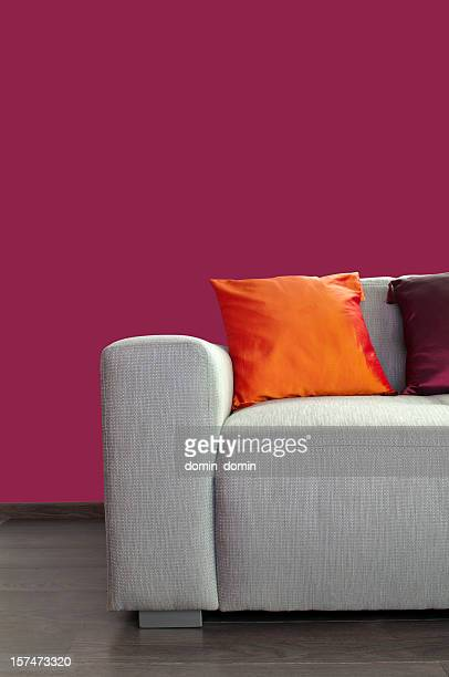Contemporary gray material sofa with pillows against purple wall