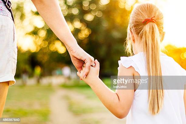 Contemporary mother and little daughter walking in park at sunset