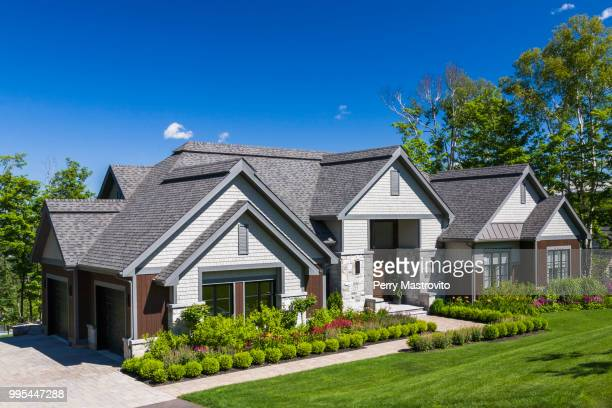 contemporary natural stone and wood luxurious bungalow style home facade - bungalow stock pictures, royalty-free photos & images