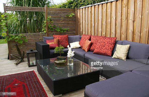 Contemporary patio with large wicker sofa. Garden design
