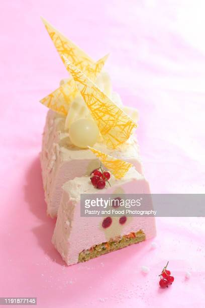 contemporary pistachio and red currant yule log cake - yule log stock pictures, royalty-free photos & images