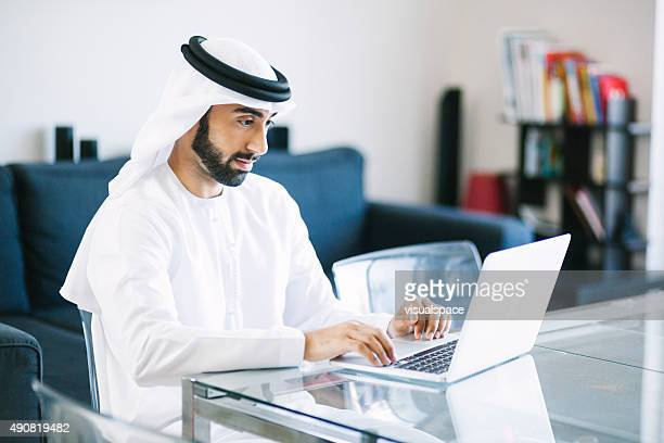 content arab man using laptop at home - united arab emirates stock pictures, royalty-free photos & images