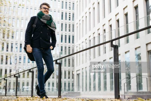 Content businessman walking in the city in autumn