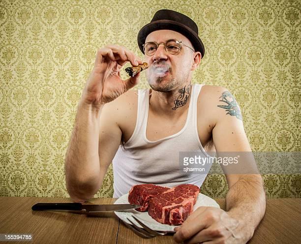 Inhalt Zigarre rauchen Mann Schneiden großes Fleisch Steak in
